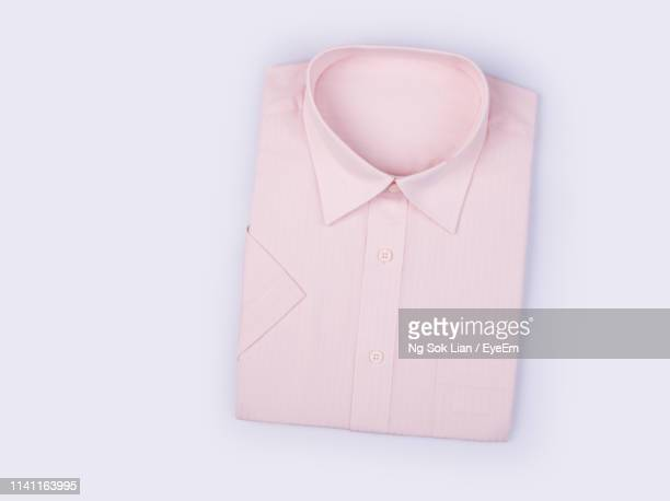 directly above shot of folded shirt on gray background - camicia foto e immagini stock