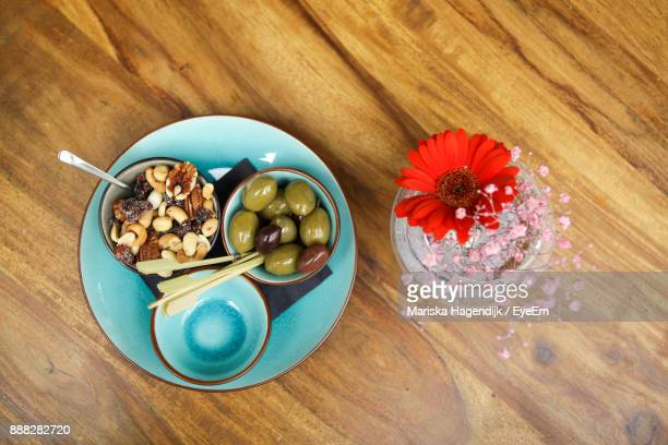 Directly Above Shot Of Food In Bowl By Flower Vase On Table