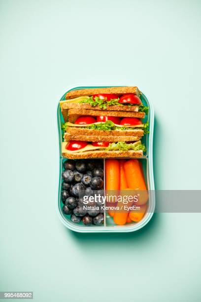 directly above shot of food in bowl over blue background - box container stock pictures, royalty-free photos & images