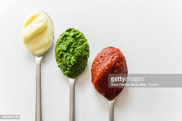directly above shot of food in spoon over white background - food dressing stock pictures, royalty-free photos & images