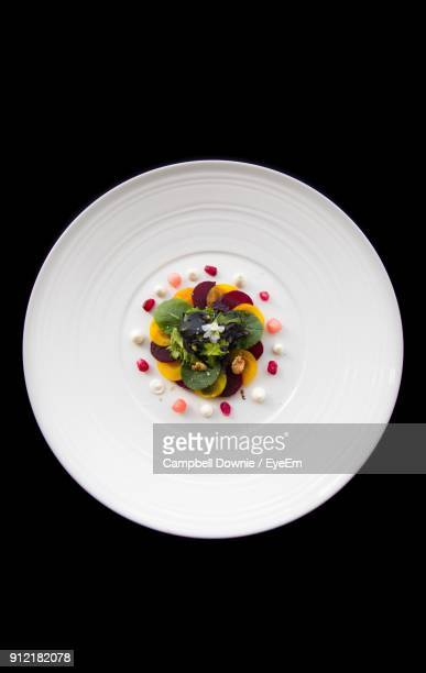 directly above shot of food in white plate over black background - campbell downie stock pictures, royalty-free photos & images