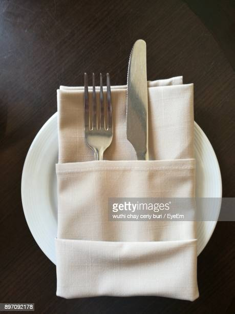 Directly Above Shot Of Fork And Knife With Napkin On Plate Over Table
