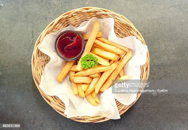 directly above shot of french fries with ketchup in wicker basket - fast food french fries stock pictures, royalty-free photos & images