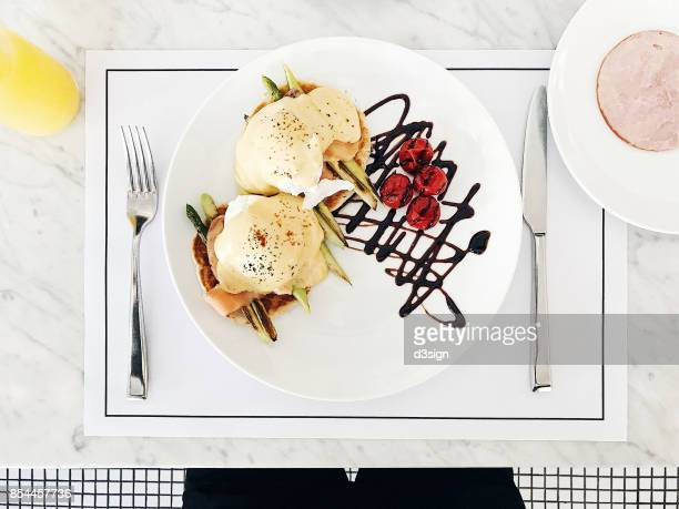 Directly above shot of freshly made Eggs Benedict and ham with orange juice served in plate