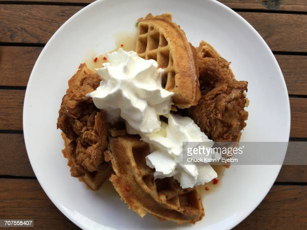 directly above shot of fried chicken and waffles with whipped cream in plate on table - chicken and waffles stock photos and pictures