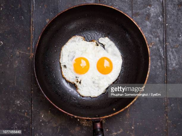 directly above shot of fried egg in cooking pan on table - fried eggs stock pictures, royalty-free photos & images