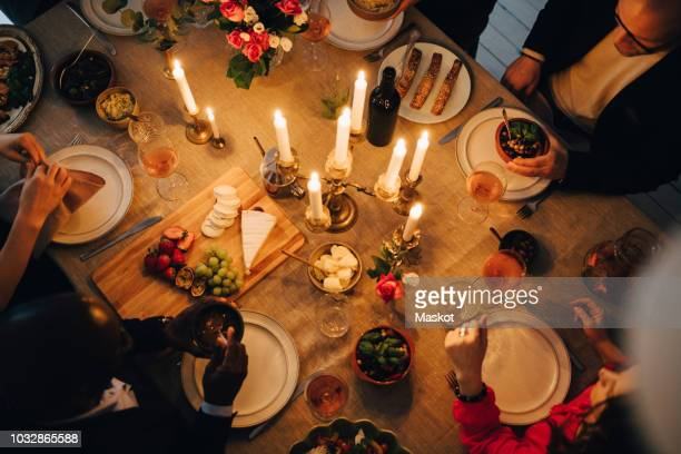 directly above shot of friends enjoying food at dinner party - dinner party stock pictures, royalty-free photos & images