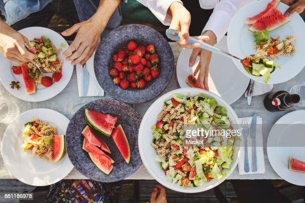 directly above shot of friends enjoying lunch at picnic table on sunny day - picnic stock pictures, royalty-free photos & images