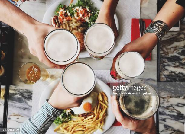 Directly Above Shot Of Friends Toasting Alcohol Glasses Over Table In Restaurant