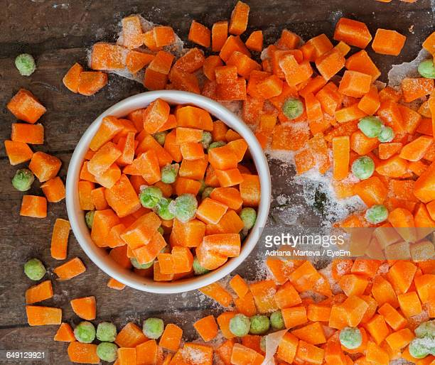 directly above shot of frozen chopped carrots and pea on table - frozen stock pictures, royalty-free photos & images