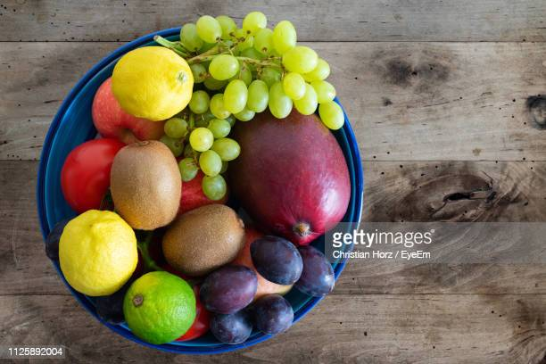 directly above shot of fruits in bowl on wooden table - 果物の盛り合わせ ストックフォトと画像