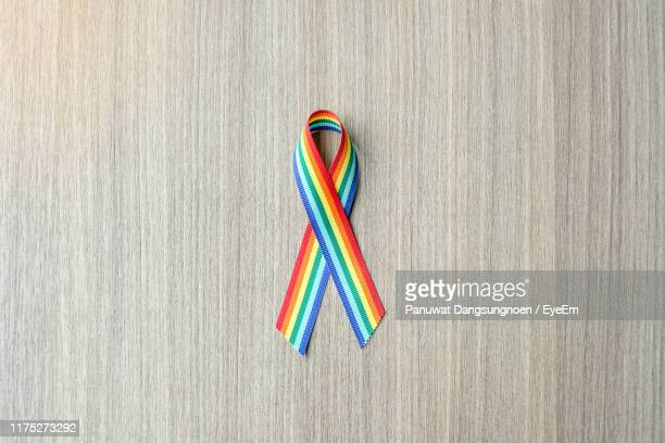 directly above shot of gay pride ribbon on wooden table - ゲイプライドのシンボル ストックフォトと画像