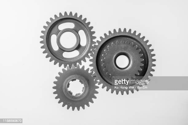 directly above shot of gear wheels against white background - gear stock pictures, royalty-free photos & images