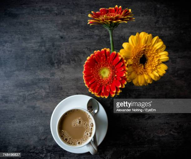 Directly Above Shot Of Gerbera Daisies By Coffee On Table