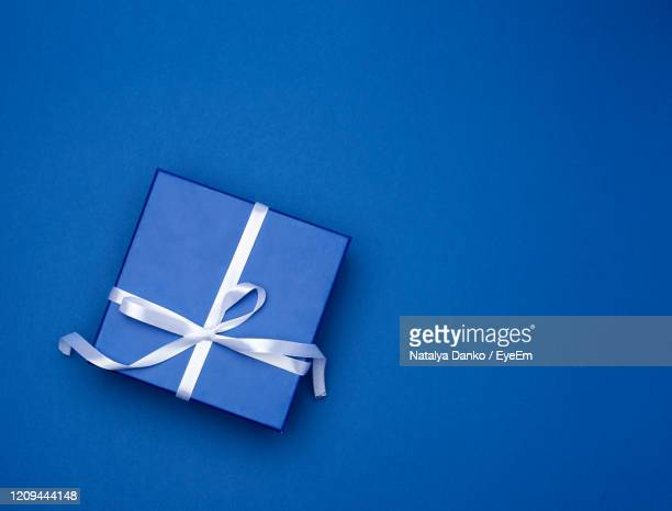 directly above shot of gift box over blue background - gift box stock pictures, royalty-free photos & images