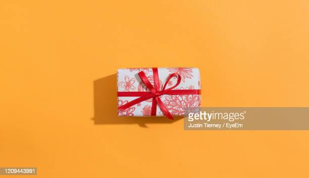 directly above shot of gift box over orange background - gifts stock pictures, royalty-free photos & images