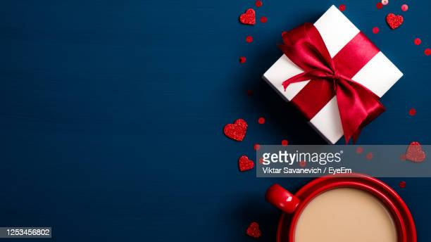 directly above shot of gift with coffee on blue background - gifts stock pictures, royalty-free photos & images