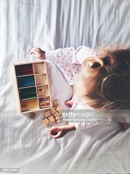 Directly Above Shot Of Girl Playing With Toy Blocks And Crayons On Bed