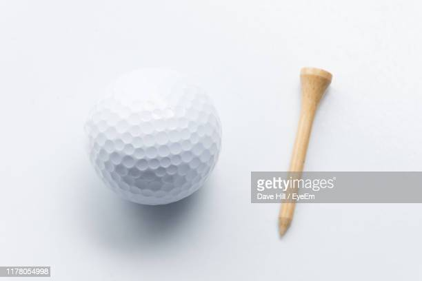 directly above shot of golf ball over white background - ゴルフのティー ストックフォトと画像