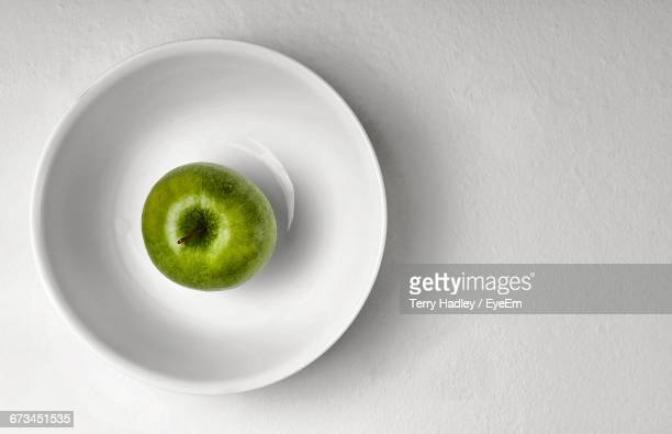 Directly Above Shot Of Granny Smith Apple In Plate Against White Background
