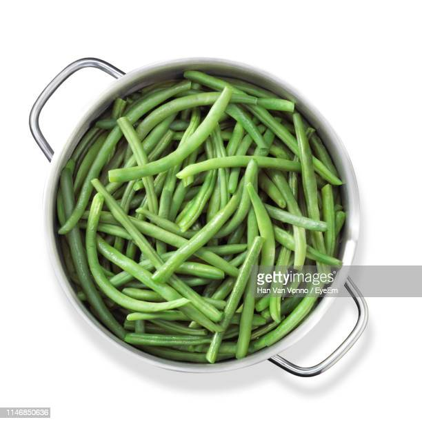 directly above shot of green beans in container on white background - green bean stock pictures, royalty-free photos & images