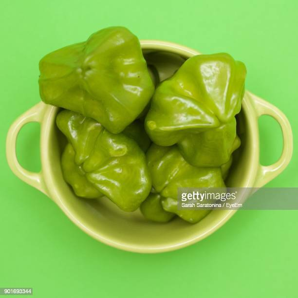 directly above shot of green bell peppers in bowl on green background - pimiento verde fotografías e imágenes de stock