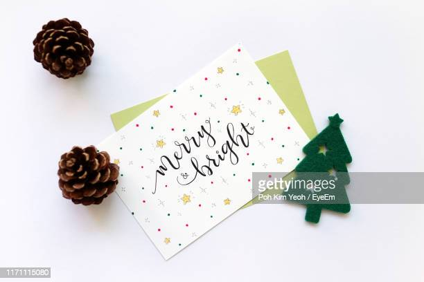 directly above shot of greeting cards with pine cones on white background - christmas card fotografías e imágenes de stock