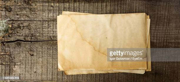 directly above shot of grunge blank papers on wooden table - igor golovniov stock pictures, royalty-free photos & images