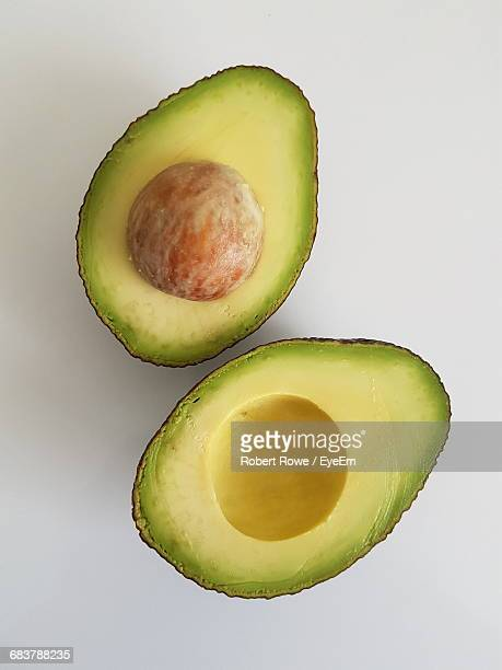 directly above shot of halved avocado on white background - avocado stock pictures, royalty-free photos & images
