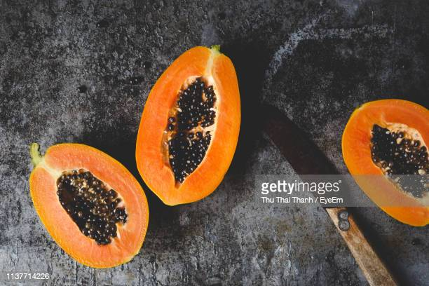 directly above shot of halved papaya slices and knife on table - papaya stock photos and pictures