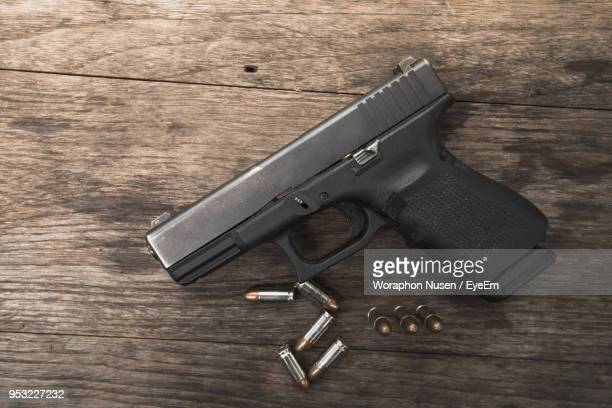 directly above shot of handgun with bullets on table - gun stock pictures, royalty-free photos & images