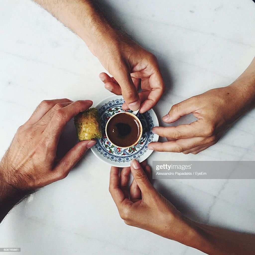 Directly Above Shot Of Hands Holding Baklava And Cup Of Chocolate : Stock Photo