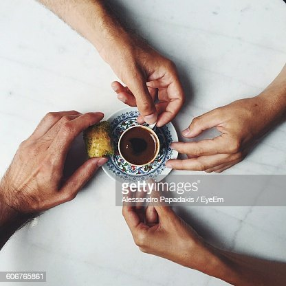 Directly Above Shot Of Hands Holding Baklava And Cup Of Chocolate