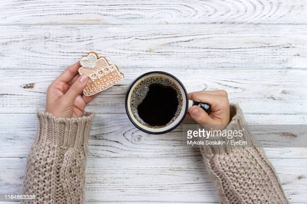 directly above shot of hands holding coffee cup and cookie on table - 袖 ストックフォトと画像