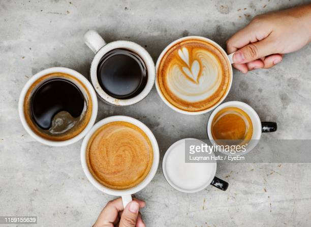 directly above shot of hands holding coffee cups on table - コーヒー ストックフォトと画像
