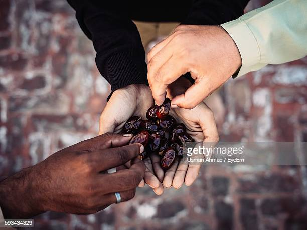 directly above shot of hands holding date fruit during ramadan - ramadan stock pictures, royalty-free photos & images