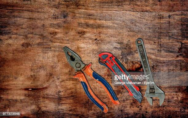 Directly Above Shot Of Hands Tools On Wooden Table