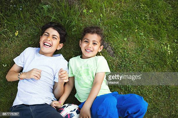 Directly above shot of happy boys lying on grassy field