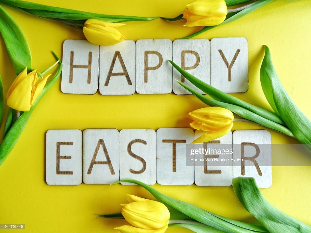 Directly Above Shot Of Happy Easter Text With Yellow Tulips On Table : Stock Photo