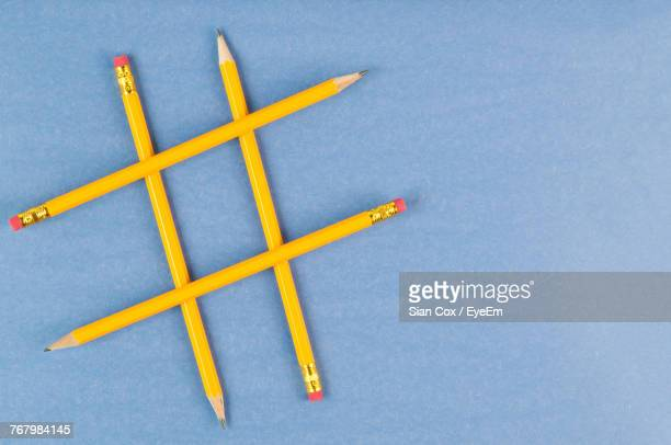 Directly Above Shot Of Hashtag Made From Yellow Pencils On Blue Background