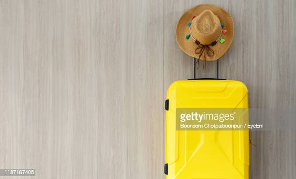 directly above shot of hat and suitcase on wall - yellow hat stock pictures, royalty-free photos & images