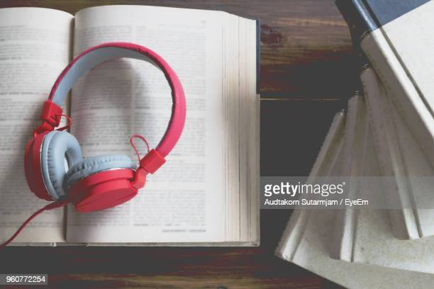 directly above shot of headphones on open book at table - audio equipment stock pictures, royalty-free photos & images