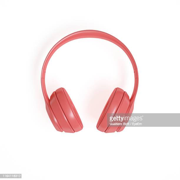 directly above shot of headphones over white background - accessoires stock-fotos und bilder