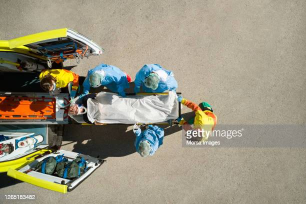 directly above shot of healthcare workers bringing patient on stretcher - ambulance stock pictures, royalty-free photos & images