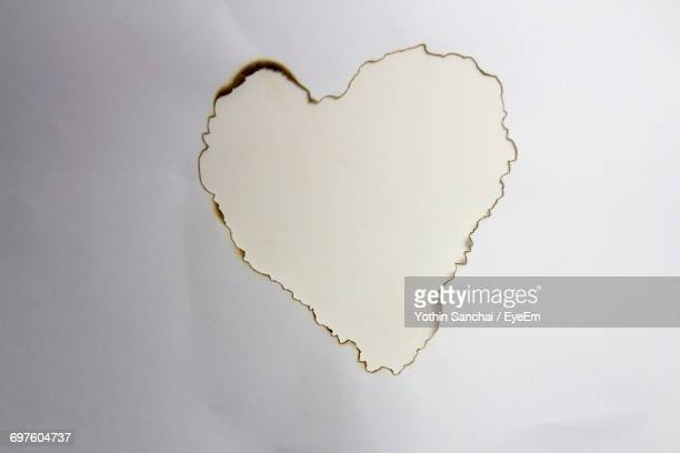 Directly Above Shot Of Heart Shape Burnt Paper On Table