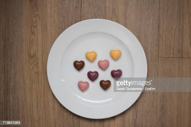 Directly Above Shot Of Heart Shape Chocolates In Plate On Wooden Table