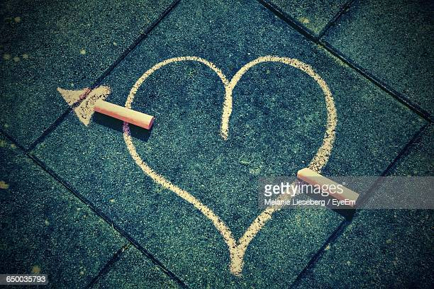 Directly Above Shot Of Heart Shape Drawn By Chalks On Footpath