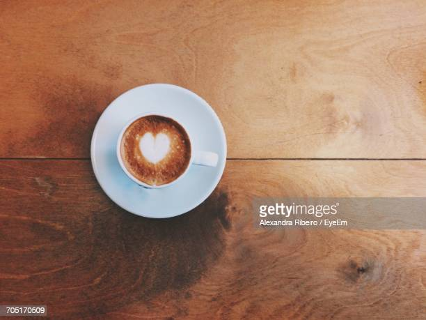 Directly Above Shot Of Heart Shape Froth Art On Coffee At Wooden Table