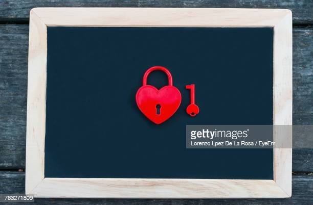 Directly Above Shot Of Heart Shape Padlock And Key On Blackboard