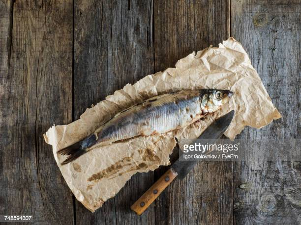 Directly Above Shot Of Herring Fish On Paper At Table
